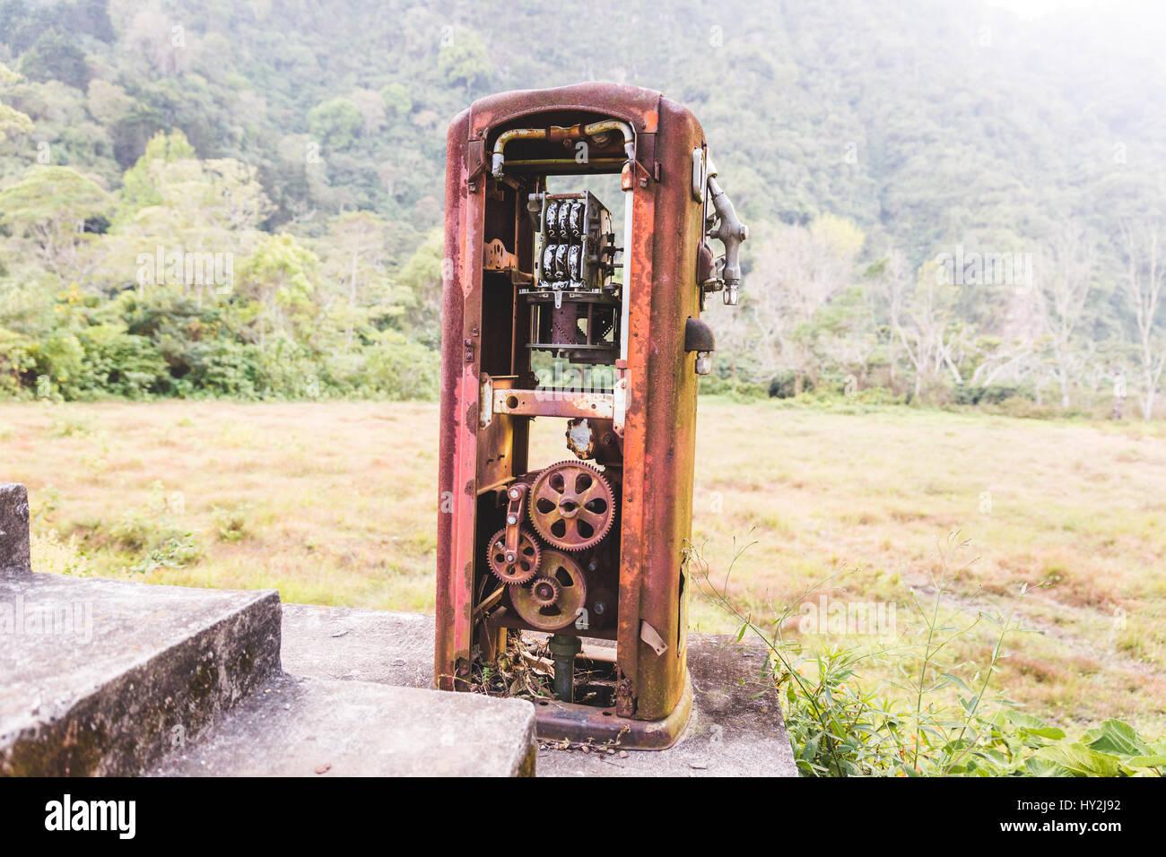 Heavily rusted, antique gas pump in the remote jungle near Lake Atitlan, Guatemala, Central America. - Stock Image