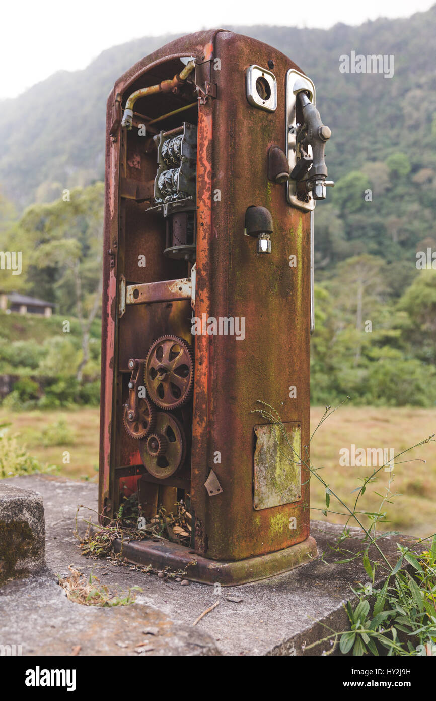 Heavily rusted, antique gas pump in the remote jungle near Lake Atitlan, Guatemala, Central America. - Stock Image