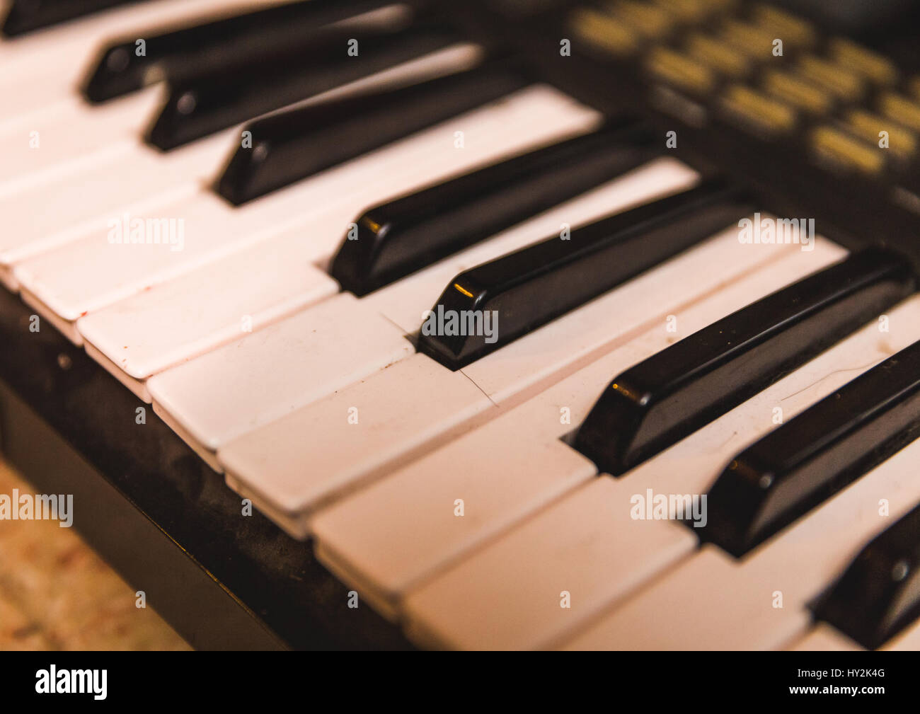 Cracked and bent keys on the keyboard of a vintage synthesizer. - Stock Image