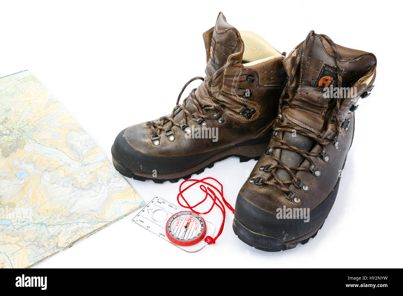 b0394477af85 A pair of used traditional leather British made Altberg hiking boots walking  map and navigation compass isolated on white. England UK Britain