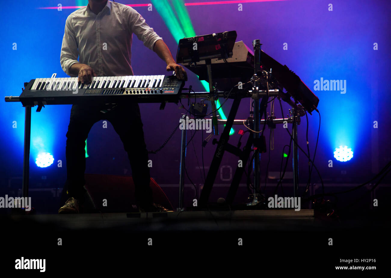 disc jokey mixing on stage over illuminated smoke background Stock Photo