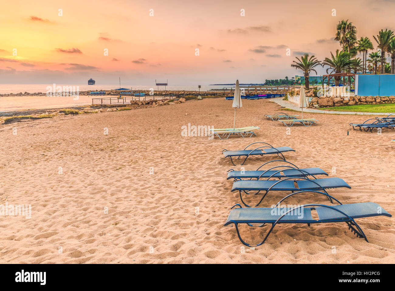 Sunset on the beach in the town of Paphos, Cyprus. View of the Mediterranean Sea and the coastline. - Stock Image