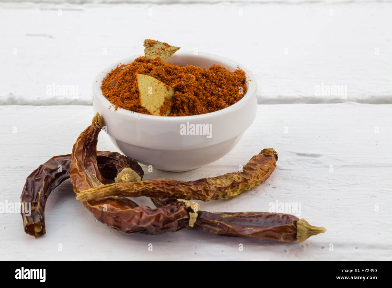 Red Chili pepper powder in white bowl with dried chili peppers on white table - Stock Image