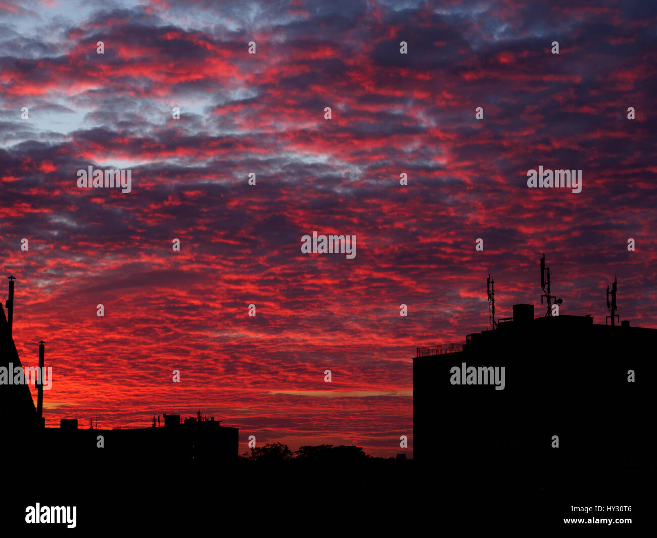Silhouette Of City Against Dramatic Sky During Sunset - Stock Image