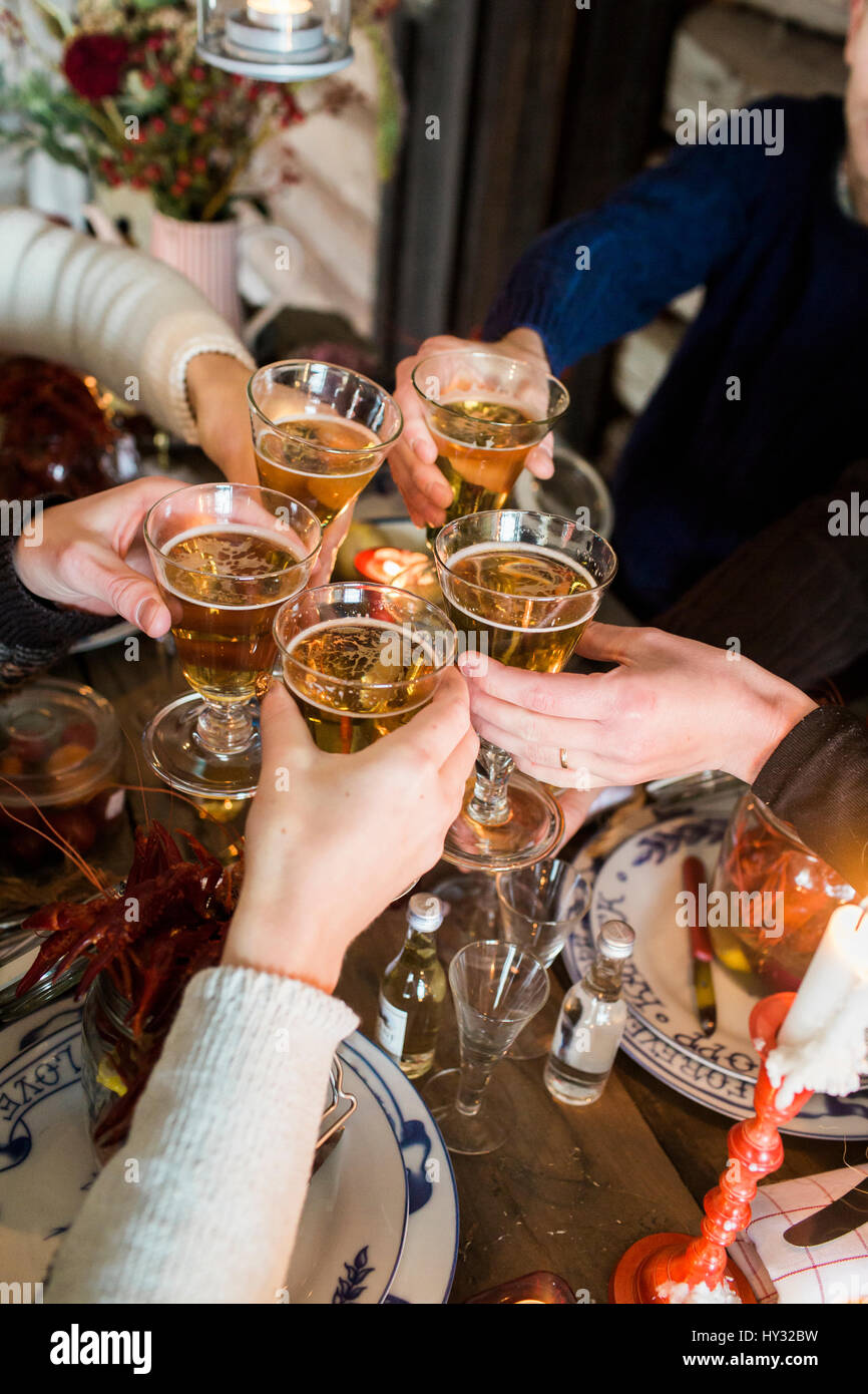 Sweden, People raising toast during crayfish party Stock Photo
