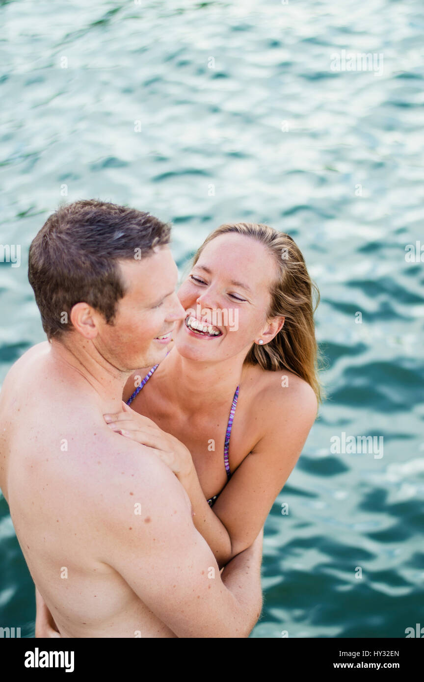 Sweden, Vastmanland, Mid adult couple embracing in sea - Stock Image