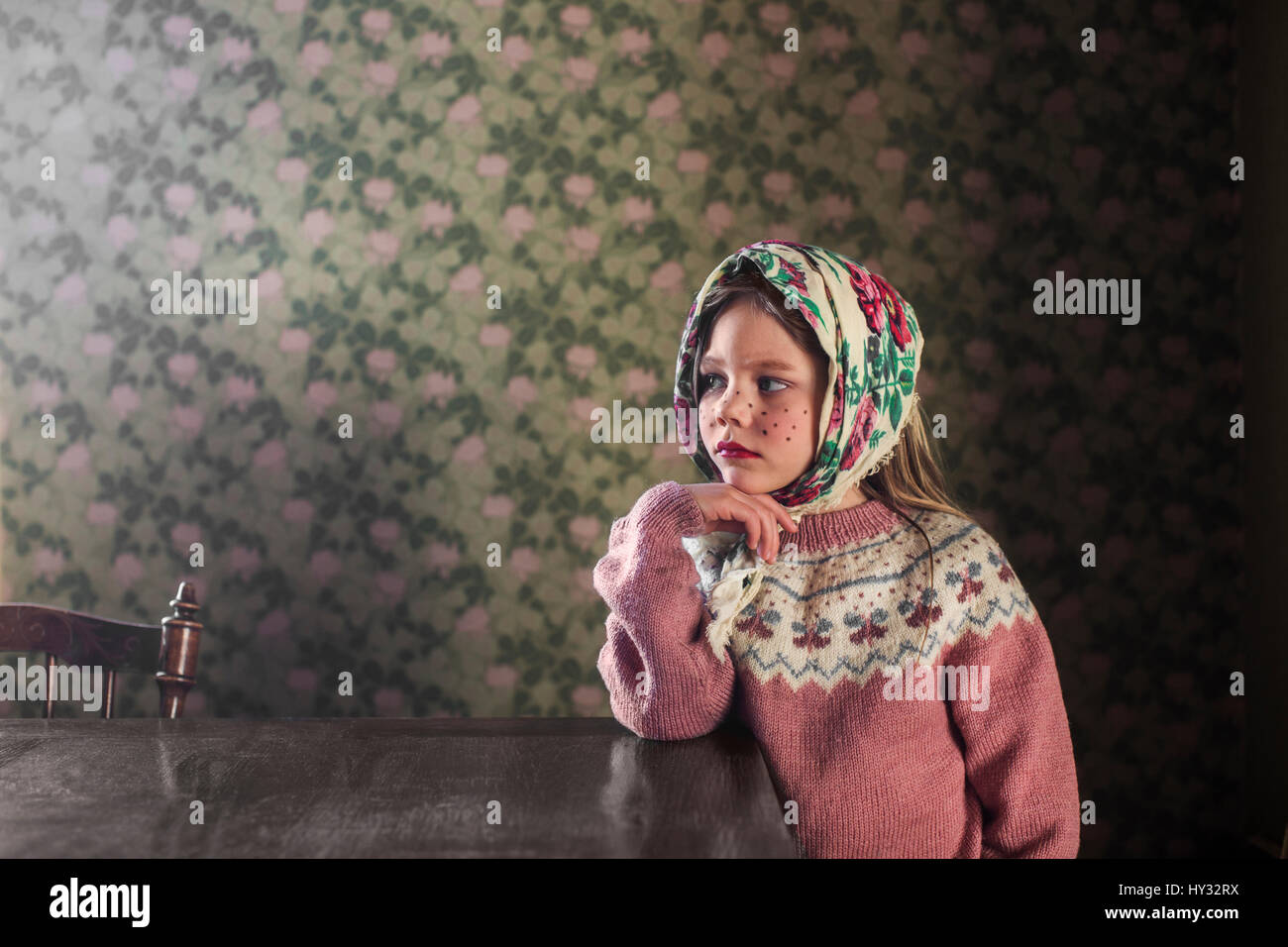 Sweden, Portrait of girl (4-5) dressed up as Easter witch leaning on table - Stock Image