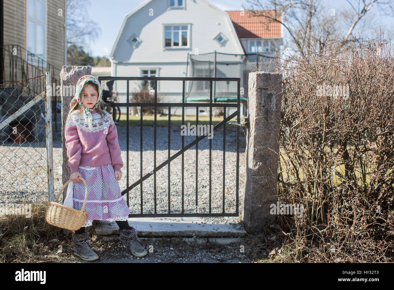 Sweden, Girl (4-5) dressed up as Easter witch with Easter basket standing by gate - Stock Image