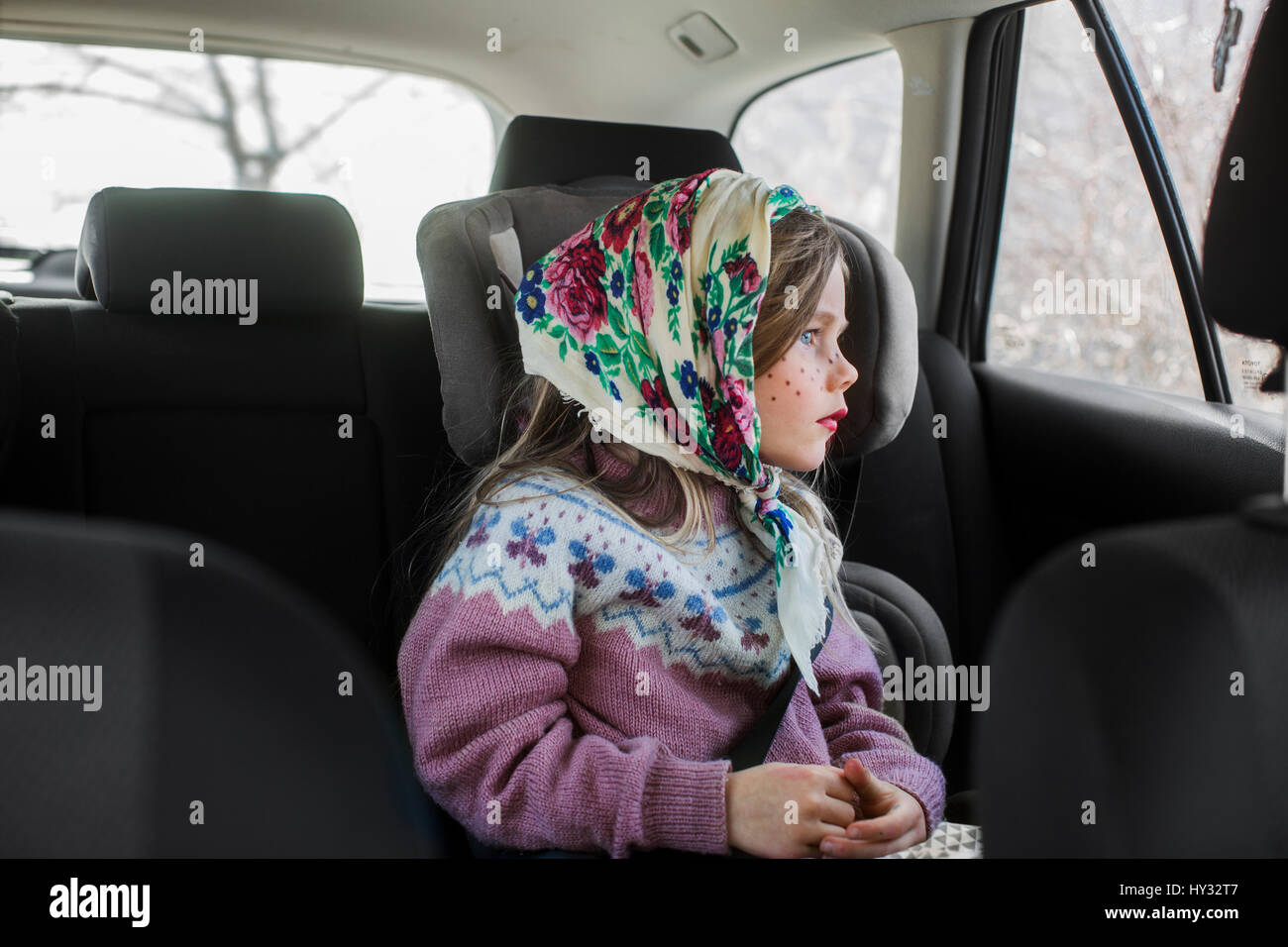 Sweden, Girl (4-5) dressed up as Easter witch sitting in car and looking through window - Stock Image