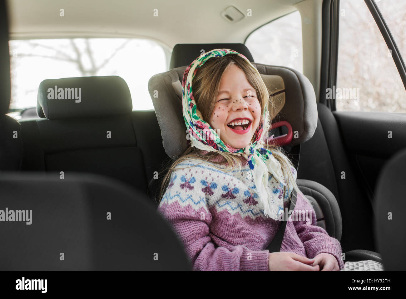 Sweden, Girl (4-5) dressed up as Easter witch wearing headscarf laughing in car - Stock Image