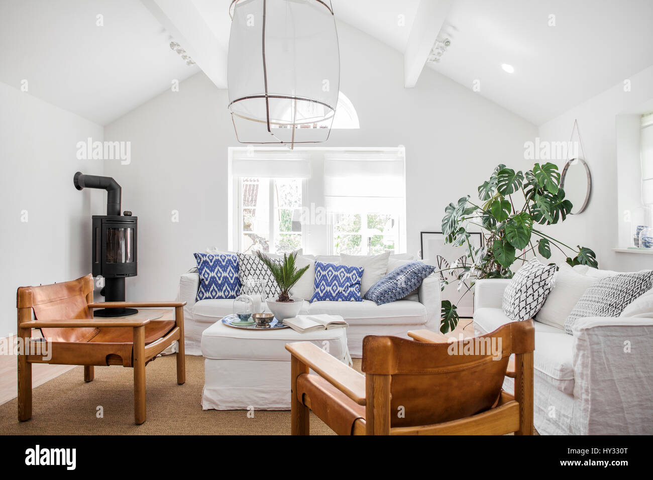 Sweden, Living room with white sofas and wooden chairs - Stock Image