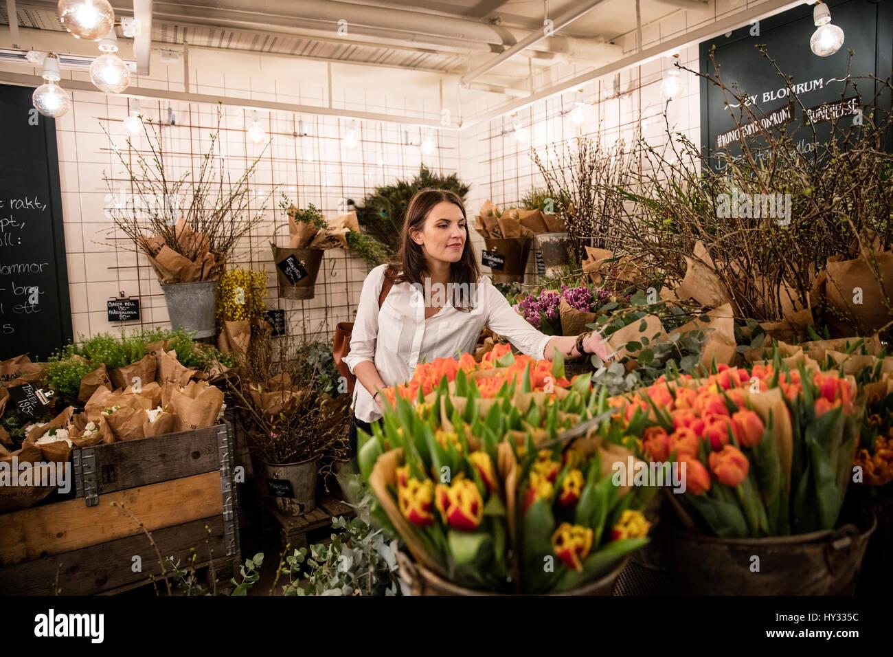 Sweden, Woman choosing flowers in shop - Stock Image