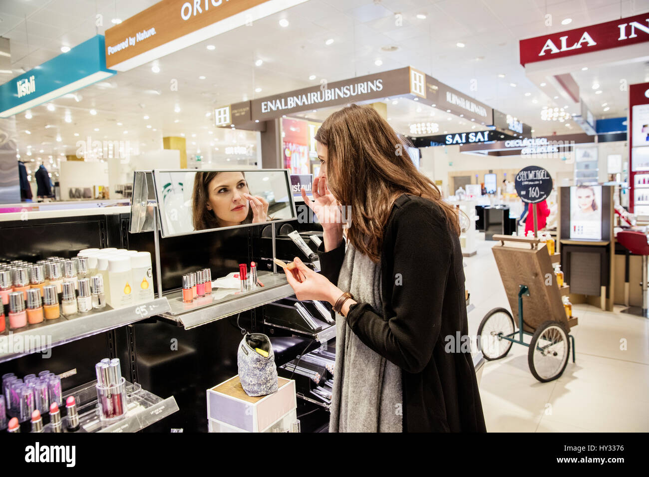 Sweden, Woman testing foundation in perfumery - Stock Image