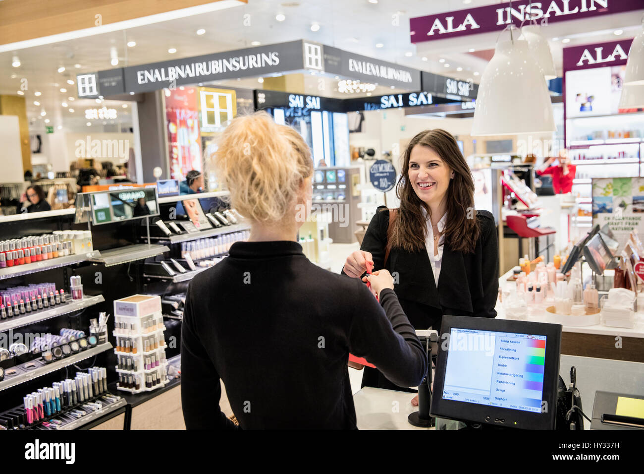 Sweden, Woman doing shopping in perfumery - Stock Image
