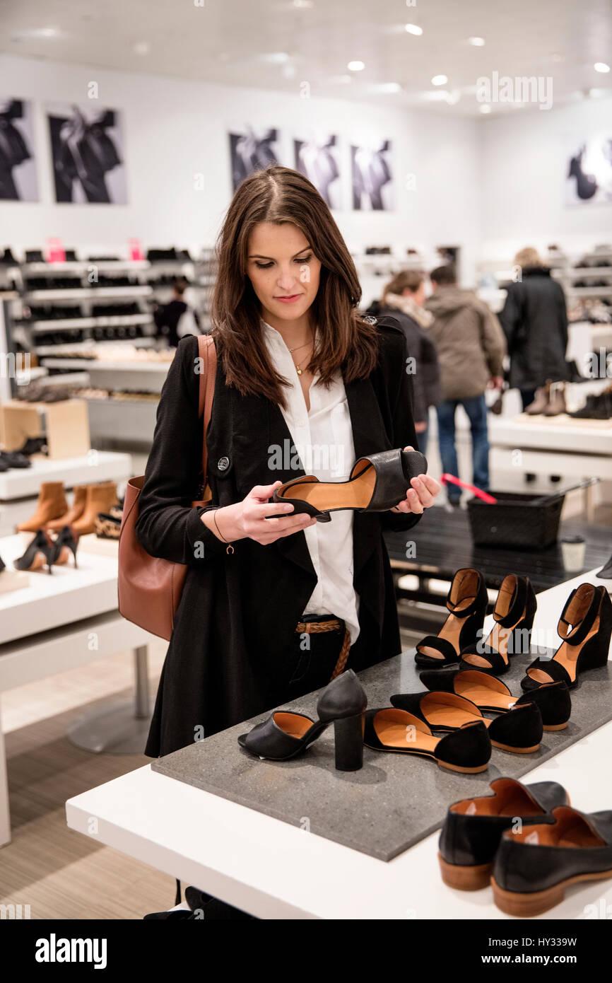 Sweden, Woman choosing shoes in shoe store - Stock Image