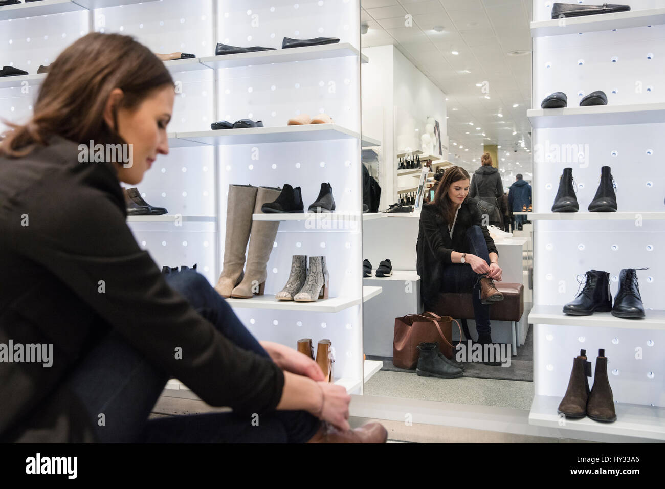 Sweden, Woman choosing shoes in store - Stock Image