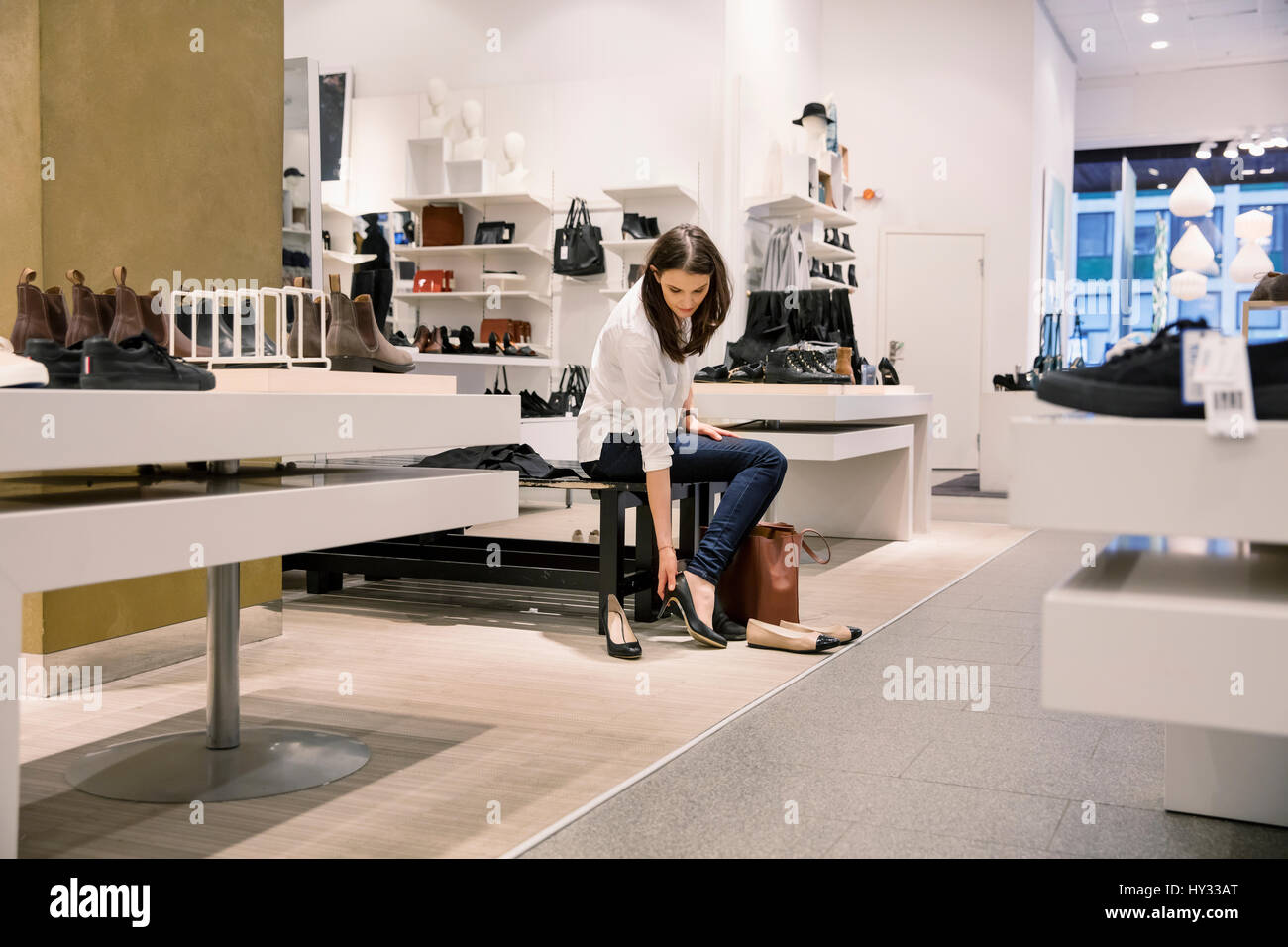 Sweden, Woman trying on shoes in store - Stock Image