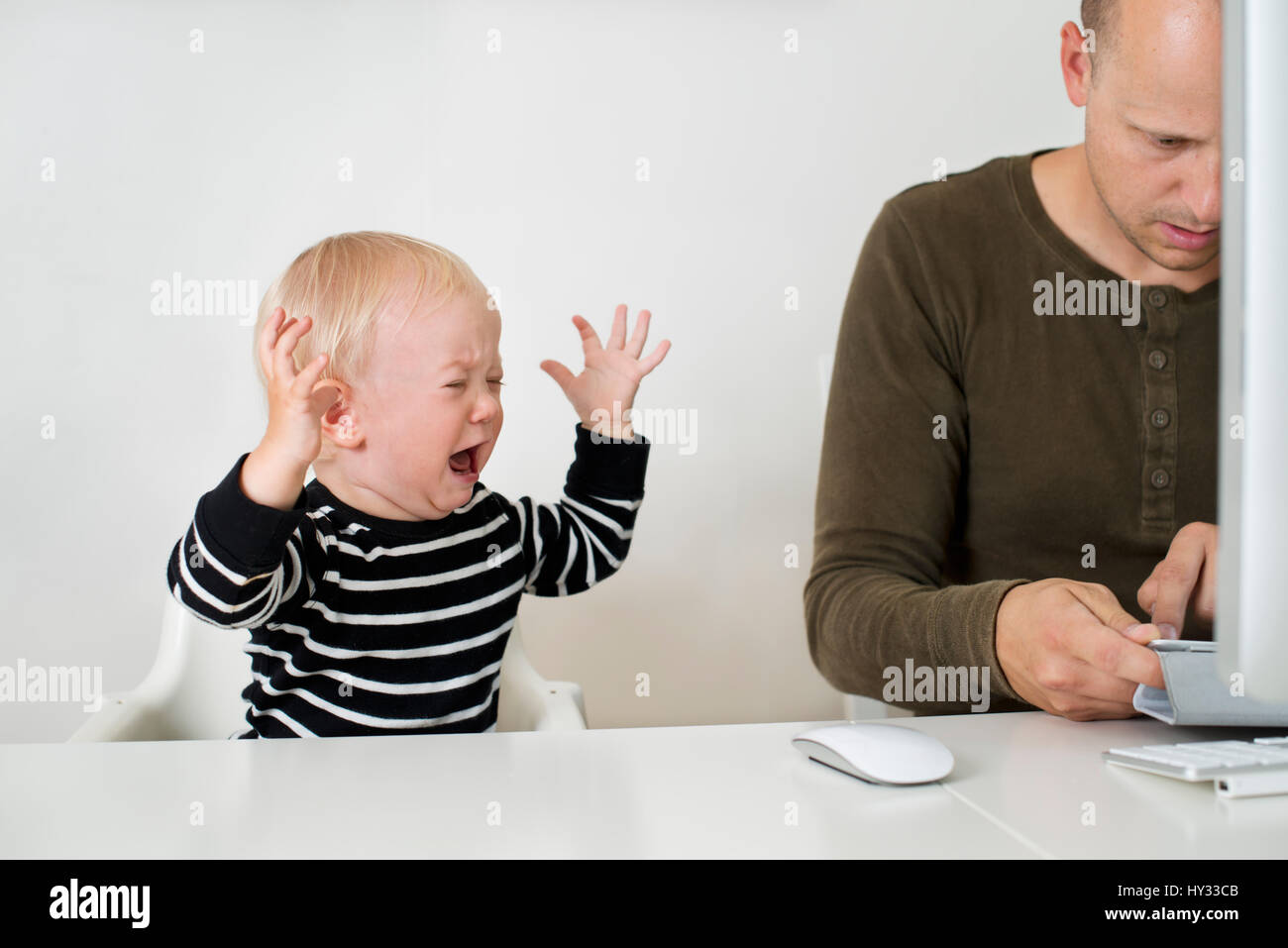 Sweden, Stay at home dad using tablet, son (12-17 months) throwing tantrums - Stock Image