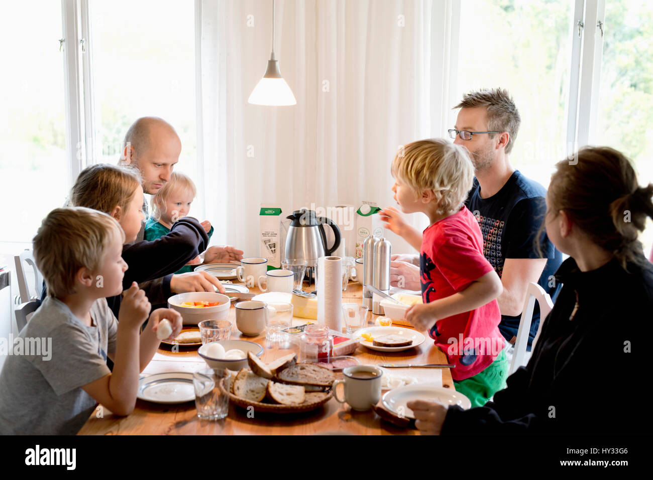 Sweden, Family with children (2-3, 4-5,10-11,16-17) eating breakfast at table - Stock Image