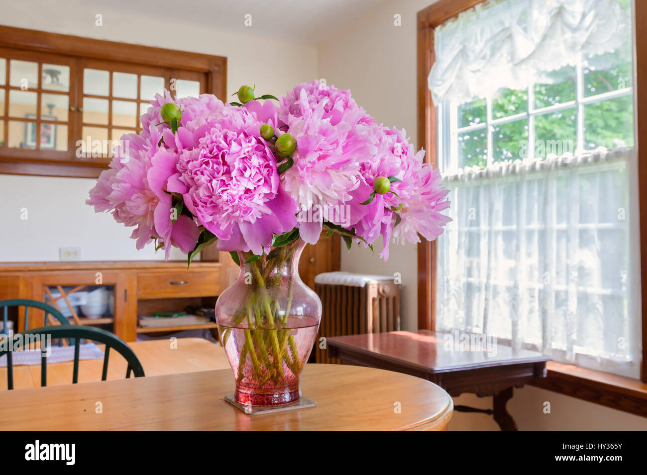 Peony bouquet in an older home interior. - Stock Image