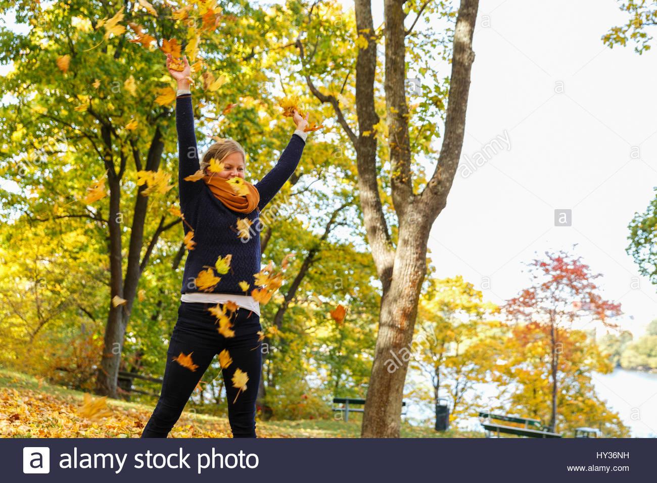 Sweden, Sodermanland, Stockholm, Sodermalm, Langholmen, Mid adult woman throwing autumn leaves - Stock Image