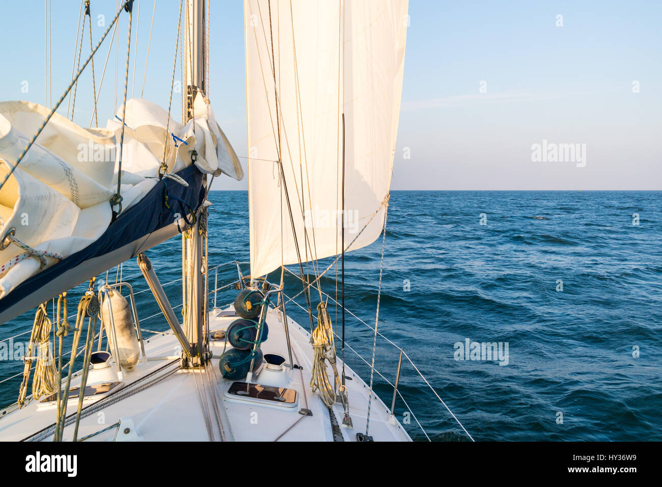 Front of sailing boat with foresail cruising on calm and sunny Waddensea, Netherlands - Stock Image