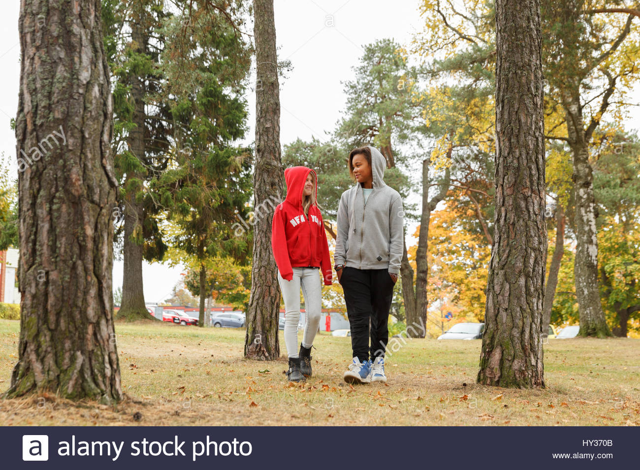 Sweden, Sodermanland, Jarna, Girls (12-13) with hoods on chatting while walking among trees - Stock Image