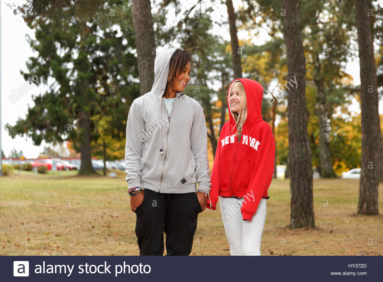 Sweden, Sodermanland, Jarna, Girls (12-13) with hoods on chatting while walking among trees Stock Photo