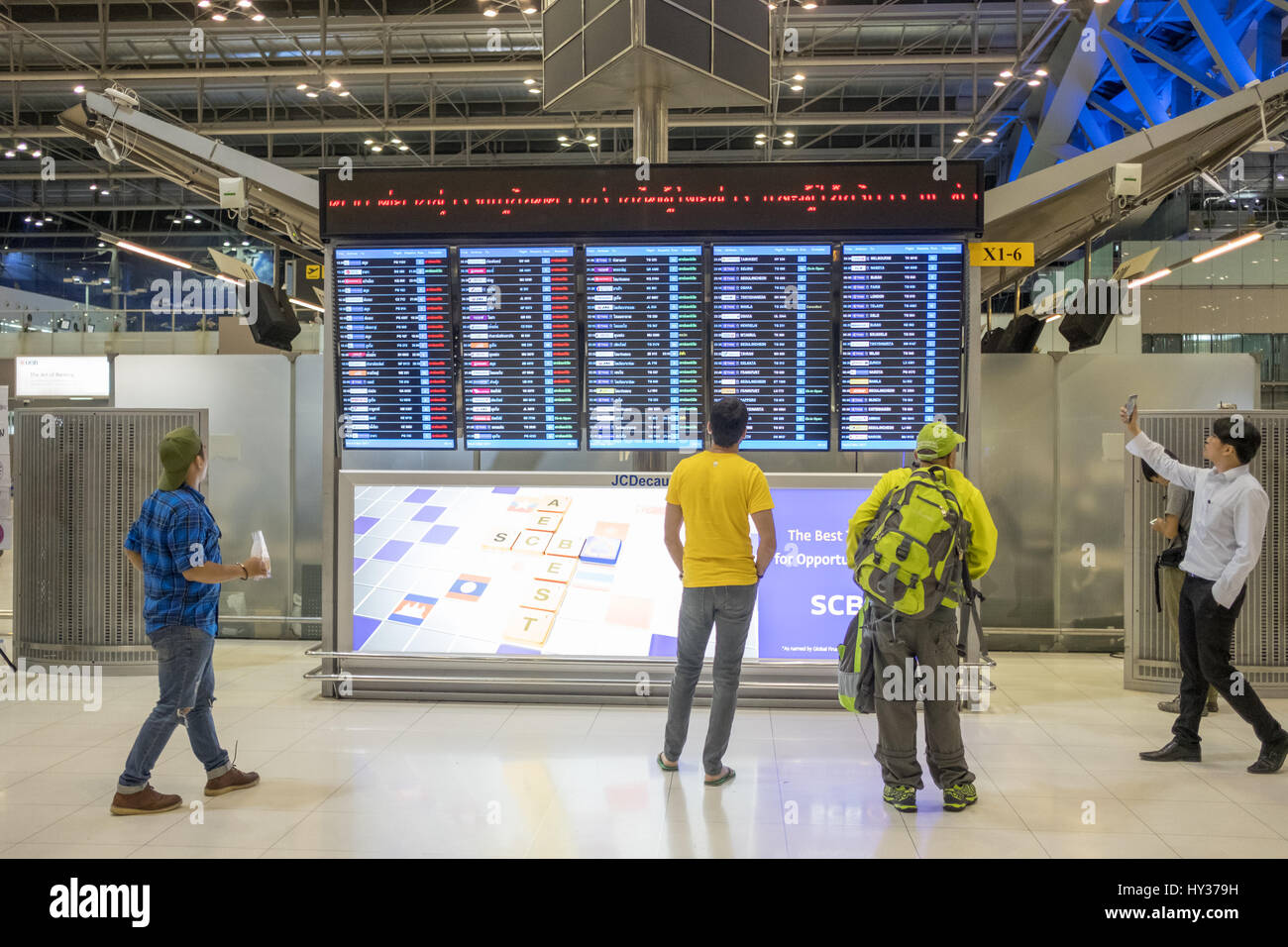 Travellers checking departures at Suvarnabhumi Airport in Bangkok. This is one of the busiest airports in the world. - Stock Image