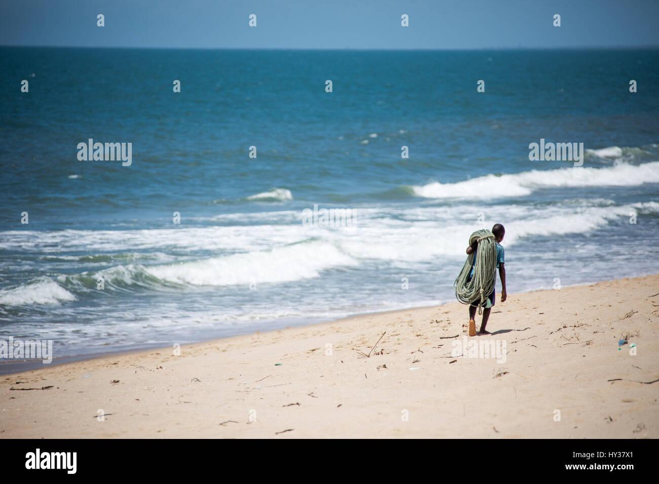 Boy carrying fishing rope on Macaneta Beach, Maputo, Mozambique - Stock Image