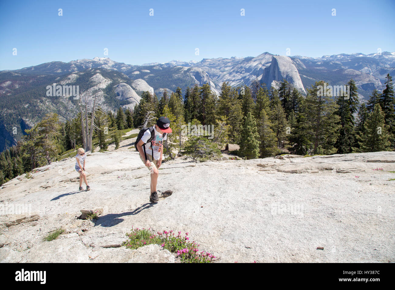 USA, California, Yosemite, Girl (12-13) and boy (14-15) walking up high mountain with view at Sentinel Dome and - Stock Image