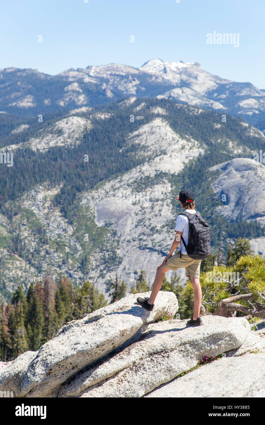 USA, California, Yosemite, Boy (14-15) looking at view with Sentinel Dome and Yosemite Falls - Stock Image