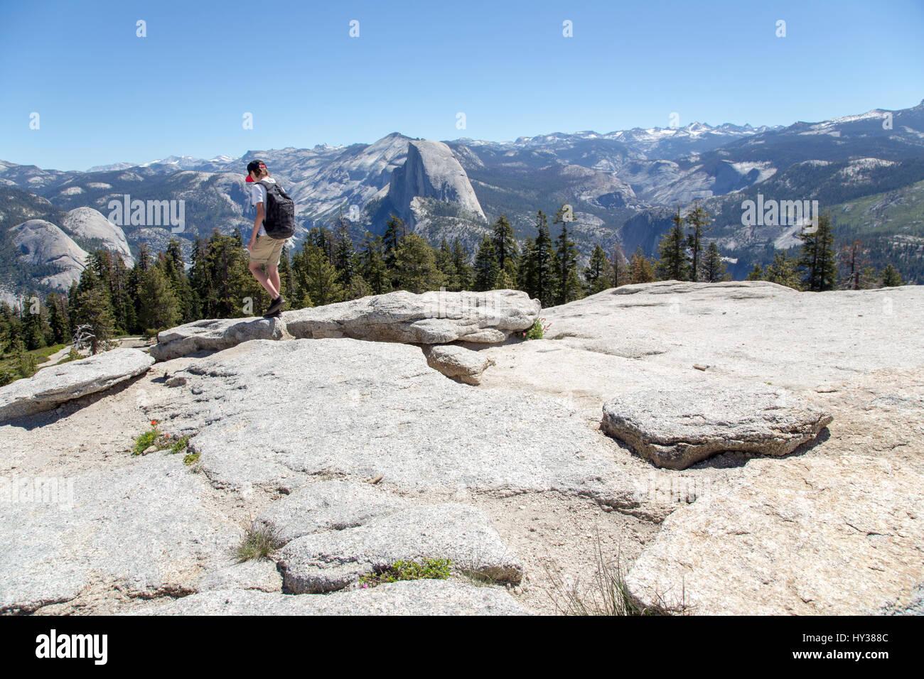 USA, California, Yosemite, Boy (14-15) during mountain trip, Sentinel Dome and Yosemite Falls in background - Stock Image