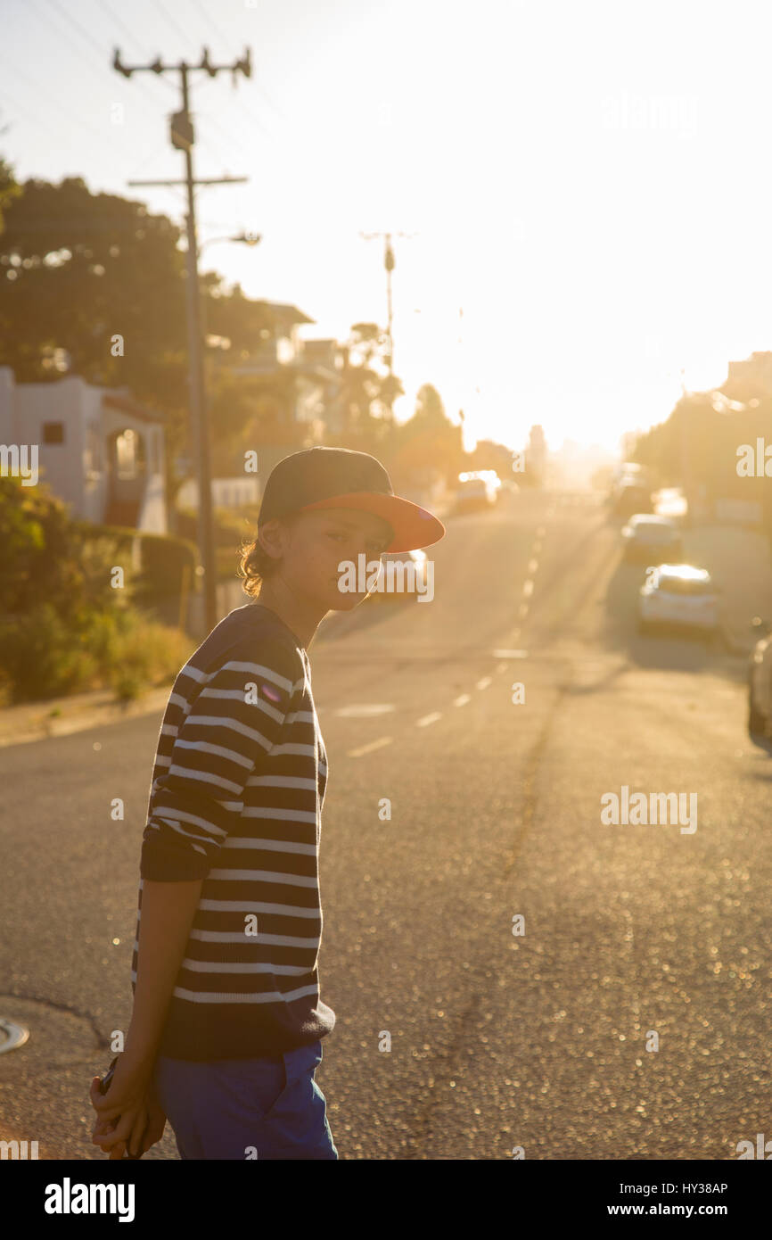 USA, California, Pacific Grove, Boy (14-15) standing on suburban road - Stock Image