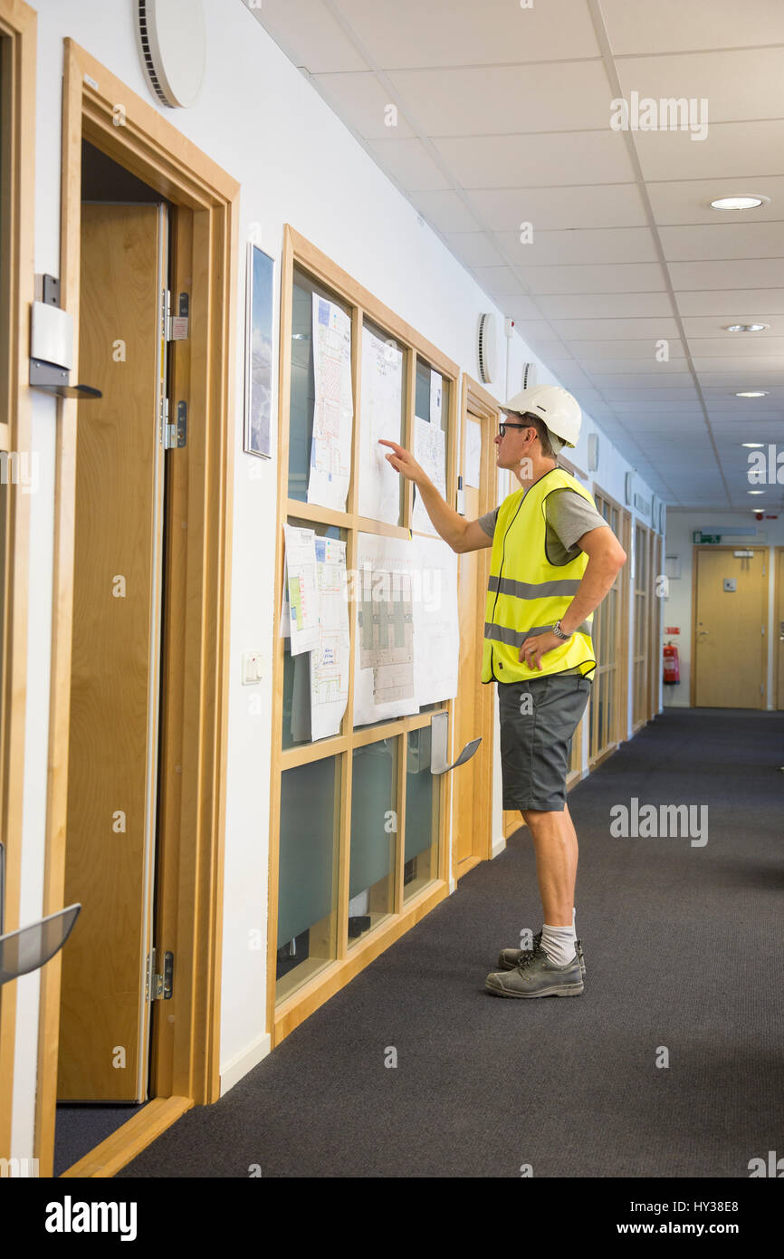 Sweden, Man wearing protective clothing standing in corridor and pointing on papers hung on wall - Stock Image