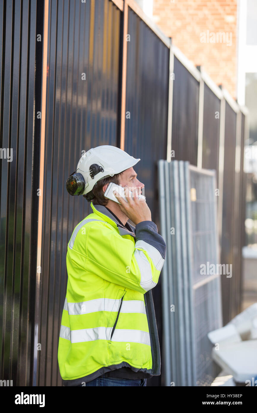 Sweden, Man using smartphone in construction site Stock Photo