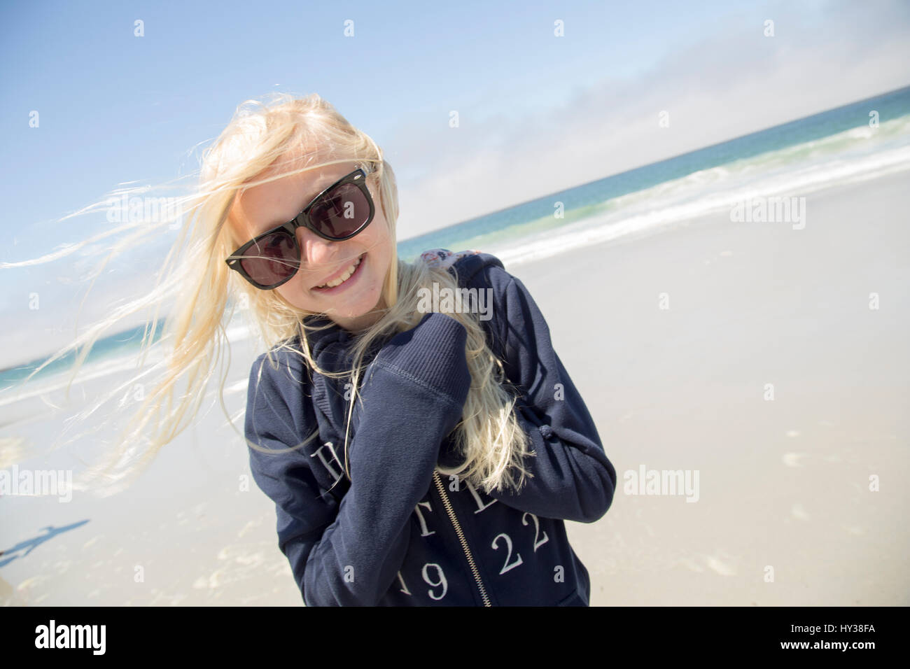 USA, California, Carmel-by-the-Sea, Smiling blonde girl (12-13) wearing sunglasses on beach - Stock Image