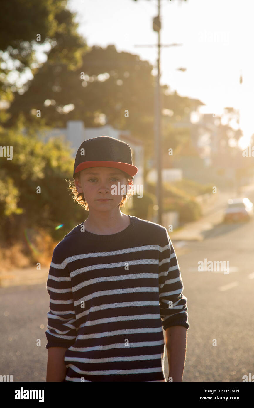 USA, California, Pacific Grove, Portrait of boy (14-15) standing in street at sunset - Stock Image