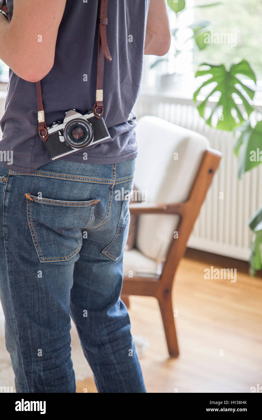 Sweden, Mid section view of mature man with photo camera - Stock Image