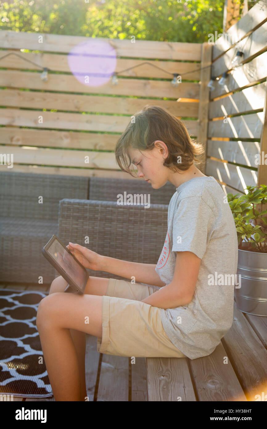 Sweden, Boy (14-15) using tablet on wooden terrace - Stock Image