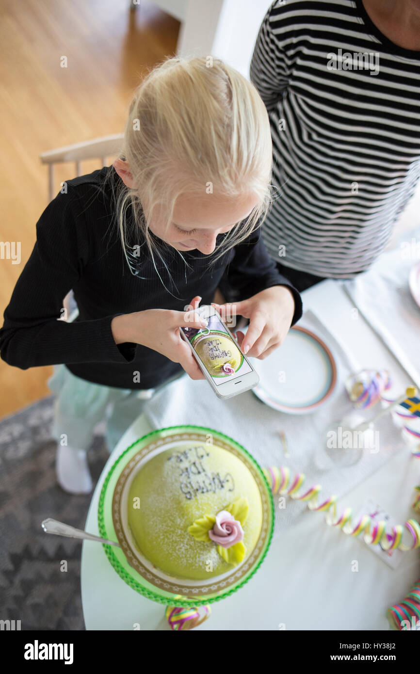 Sweden, Girl (12-13) photographing birthday cake with cell phone - Stock Image