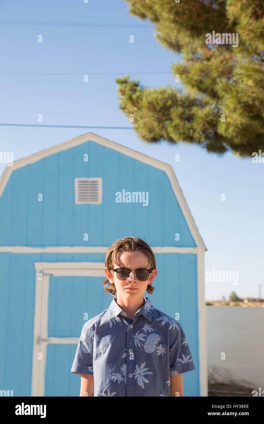 USA, California, Boy (14-15) wearing sunglasses standing in front of blue barn - Stock Image