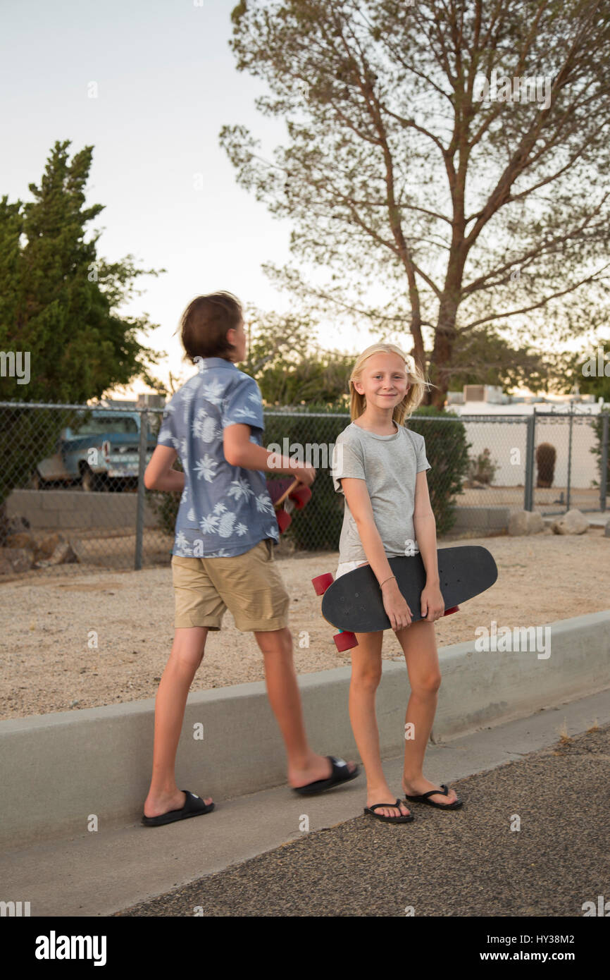 USA, California, Boy (14-15) and girl (12-13) with skateboards in street - Stock Image