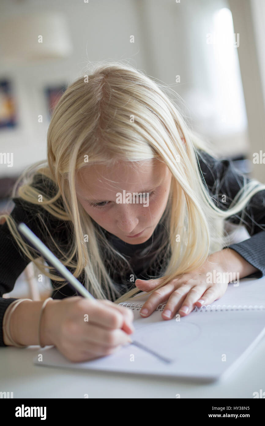 Sweden, Girl (12-13) writing in notebook - Stock Image