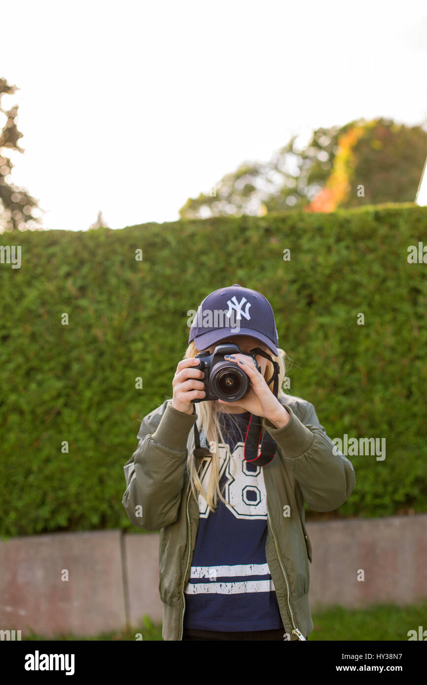 Sweden, Girl (12-13) taking photos outdoors - Stock Image