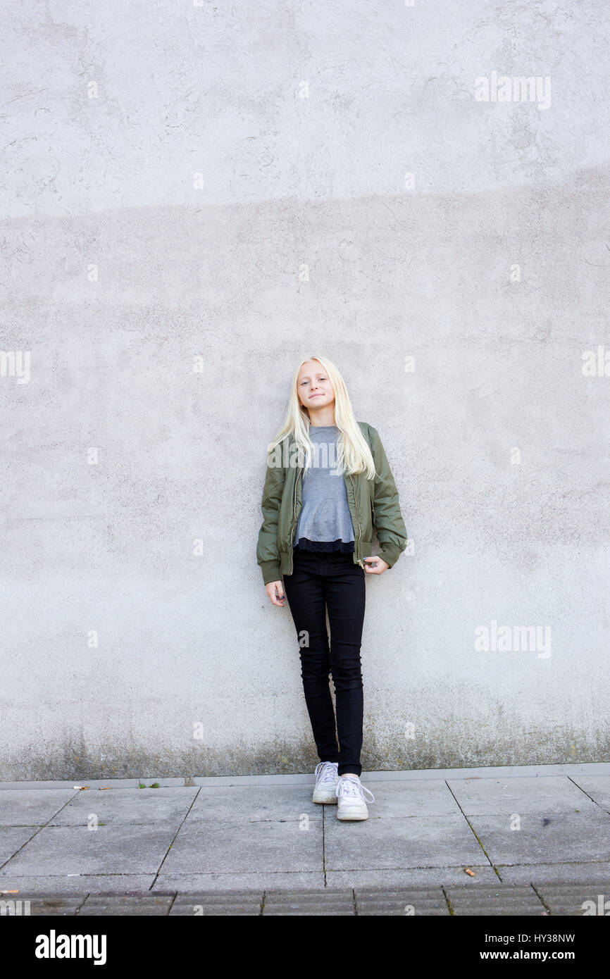 Sweden, Portrait of girl (12-13) standing against concrete wall - Stock Image