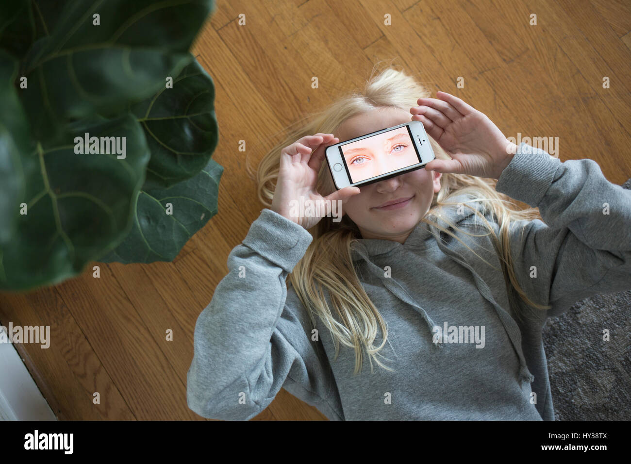 Sweden, Girl (12-13) lying on floor and covering eyes with smart phone with eyes on screen - Stock Image