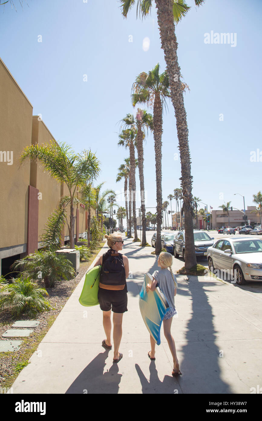 USA, California, San Diego, Woman and girl walking down sidewalk with palm trees along it and carrying surfboards - Stock Image