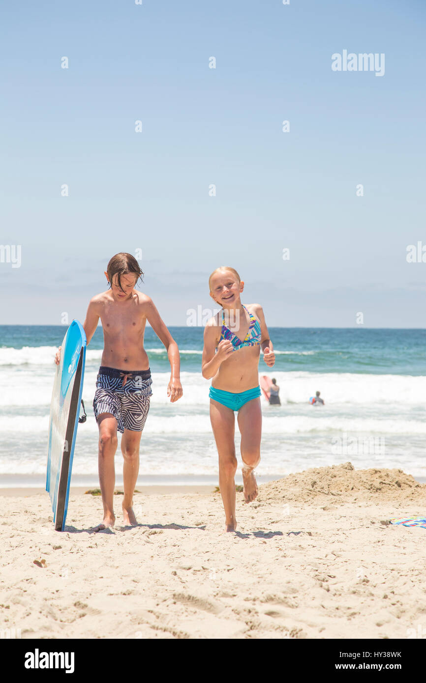 USA, California, San Diego, Boy (14-15) with surfboard and girl (12-13) walking on beach - Stock Image