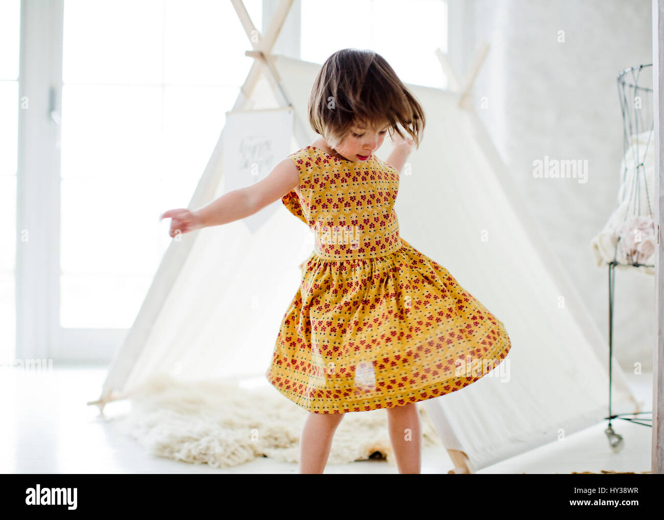 Sweden, Girl (4-5) dancing next to tent at home - Stock Image